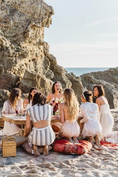 groupe de copines qui rigolent sur la plage pendant un pique nique